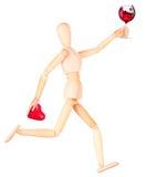 Simulacre en bois avec du vin tenant le coeur rouge Images libres de droits