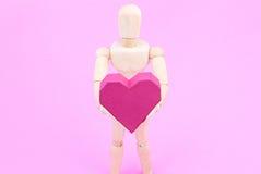 Simulacre en bois tenant la forme rouge de coeur de boîte de papier sur le backgroun rose Photo stock