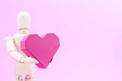 Simulacre en bois tenant la forme rouge de coeur de boîte de papier sur le backgroun rose Photos stock