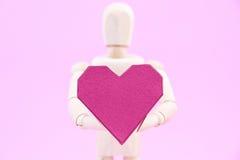 Simulacre en bois tenant la forme rouge de coeur de boîte de papier sur le backgroun rose Photos libres de droits