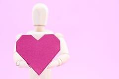 Simulacre en bois tenant la forme rouge de coeur de boîte de papier sur le backgroun rose Images stock