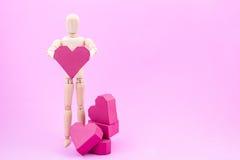 Simulacre en bois tenant la forme rouge de coeur de boîte de papier sur le backgroun rose Images libres de droits