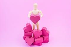 Simulacre en bois tenant la forme rouge de coeur de boîte de papier sur le backgroun rose Image libre de droits