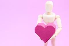 Simulacre en bois tenant la forme rouge de coeur de boîte de papier sur le backgroun rose Photo libre de droits