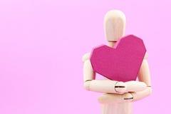 Simulacre en bois tenant la forme rouge de coeur de boîte de papier sur le backgroun rose Photographie stock libre de droits