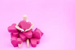 Simulacre en bois tenant la forme rouge de coeur de boîte de papier sur le backgroun rose Photographie stock