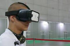 Simulador de voo vestindo adolescente dos testes do dispositivo da realidade virtual fotos de stock