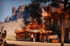 Simulation of a city fire of an old wild western wooden building in a gold mine royalty free stock photos