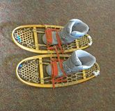 Simulation of how to put shoes on a retro rackets to walk on snow or snowshoes, winter sports and outdoor activities. royalty free stock images