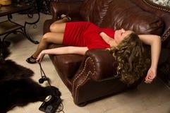 Simulazione della scena del crimine: menzogne bionda senza vita sul sofà Fotografia Stock