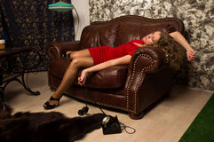 Simulazione della scena del crimine: menzogne bionda senza vita sul sofà Fotografie Stock Libere da Diritti