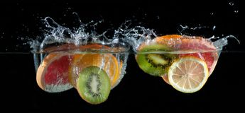 Sinaasappel, citroen, grapefruit en kalk het bespatten in water stock foto's