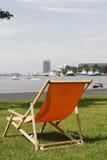 Sinaasappel deckchair in gras met mening over bezige rivier Royalty-vrije Stock Fotografie