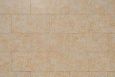 Sinaasappel die tegels onder ogen zien die van steen op de muur van het gebouw worden gemaakt stock afbeelding