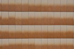 Sinaasappel die tegels onder ogen zien die van steen op de muur van het gebouw worden gemaakt stock foto