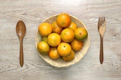 Sinaasappel in een mand en met een lepel, een houten vork Zij aan zij geplaatst en mooie houten achtergrond stock foto