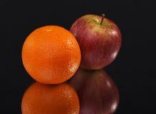 Sinaasappel en appel op zwarte achtergrond royalty-vrije stock afbeeldingen