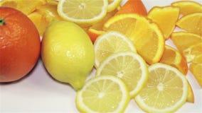Sinaasappel en citroenomwenteling op de lijst, close-up stock videobeelden