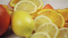 Sinaasappel en citroenomwenteling op de lijst, close-up stock footage