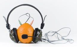 Sinaasappel en hoofdtelefoons Stock Afbeelding