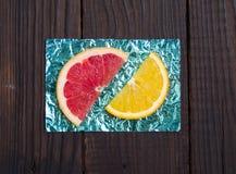 Sinaasappel en plak en grapefruit op tribunes van gekleurde folie worden gemaakt die Royalty-vrije Stock Foto