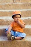 Sinaasappel geklede jongenszitting op oude stappen Stock Fotografie