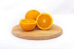 Sinaasappel gezet op het hakkende blok Royalty-vrije Stock Afbeeldingen