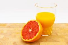 Sinaasappel of grapefruit dichtbij een glas jus d'orange Royalty-vrije Stock Foto