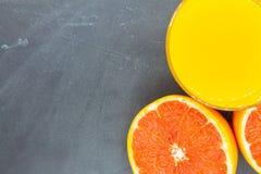 Sinaasappel of grapefruit dichtbij een glas jus d'orange Royalty-vrije Stock Afbeeldingen