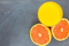 Sinaasappel of grapefruit dichtbij een glas jus d'orange Stock Afbeeldingen