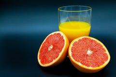 Sinaasappel of grapefruit dichtbij een glas jus d'orange Royalty-vrije Stock Foto's