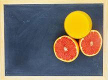 Sinaasappel of grapefruit dichtbij een glas jus d'orange Royalty-vrije Stock Afbeelding