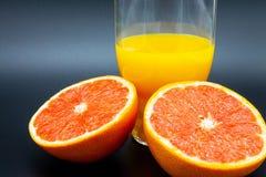 Sinaasappel of grapefruit dichtbij een glas jus d'orange Stock Foto's