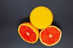 Sinaasappel of grapefruit dichtbij een glas jus d'orange Stock Fotografie