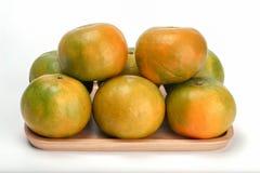 Sinaasappel in houten plaat, Thais die fruit op witte achtergrond wordt geïsoleerd royalty-vrije stock afbeelding