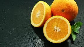 Sinaasappel met blad op natte lijst stock videobeelden