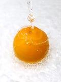 Sinaasappel met waterplons Stock Foto's
