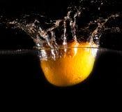 Sinaasappel onder water op een zwarte achtergrond royalty-vrije stock foto