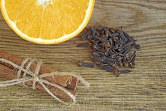 Sinaasappel, pijpjes kaneel, kruidnagels op houten achtergrond stock afbeelding