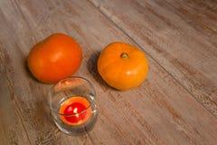Sinaasappel pumkins met kleurrijke kaars in het glas op de houten raad stock fotografie