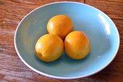 3 sinaasappelen in Blauwe Kom Stock Afbeelding