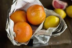 Sinaasappelen, citroenen in document op houten achtergrond Royalty-vrije Stock Foto