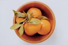 Sinaasappelen in de houten kom stock afbeeldingen