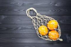 Sinaasappelen in de natuurlijke zak van het hennepkoord op een donkere houten achtergrond De ruimte van het exemplaar stock afbeelding