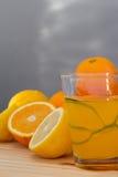 Sinaasappelen en citroen met plakken en glas vers jus d'orange Royalty-vrije Stock Afbeelding