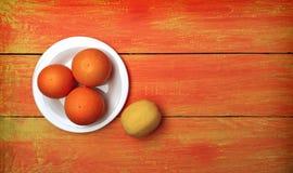 Sinaasappelen en citroen op een plaat op een heldere houten achtergrond bovenkant Royalty-vrije Stock Afbeelding