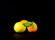 Sinaasappelen en citroen op een zwarte achtergrond, gezonde vruchten Royalty-vrije Stock Foto