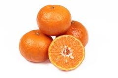 3 sinaasappelen en de oranje helften op witte achtergrond Stock Foto's