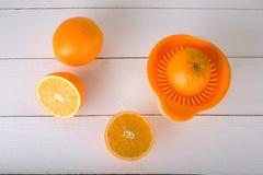 Sinaasappelen en een juicer op een witte houten achtergrond Royalty-vrije Stock Foto