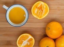 Sinaasappelen en een kop van jus d'orange op een houten raad royalty-vrije stock foto